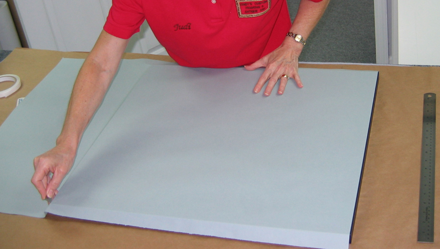 Application of acid free dust cover as part of conservation picture framing